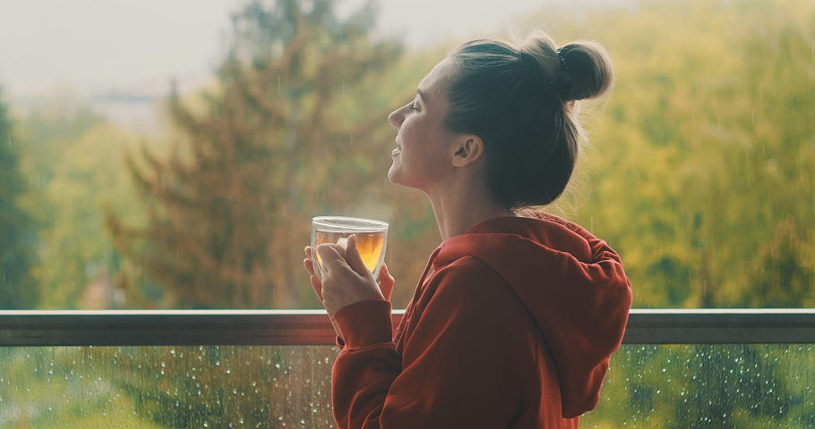 Woman drinks tea a cup, and relax on terrace at home in autumn rainy day. Health care, authenticity, sense of balance and calmness. Work from home. 4K Video Royalty-Free Stock Footage #1058414098