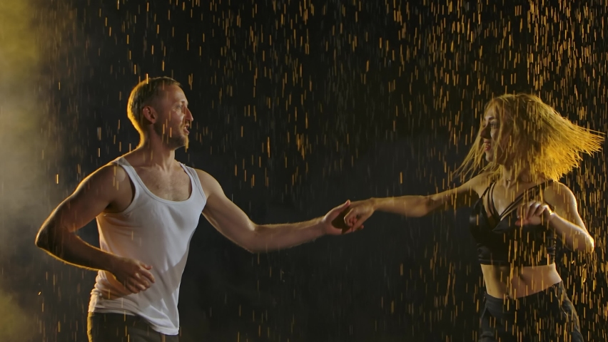Man and woman, wet from the rain, dance a passionate and graceful salsa dance. Raindrops glisten on a black background in the studio light. Slow motion. Close up.