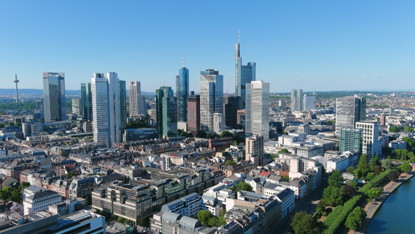 Aerial view of city skyline of Frankfurt am Main, cityscape with modern buildings (skyscrapers) with clear blue sky behind them - landscape panorama of Germany from above, Europe Royalty-Free Stock Footage #1058418892