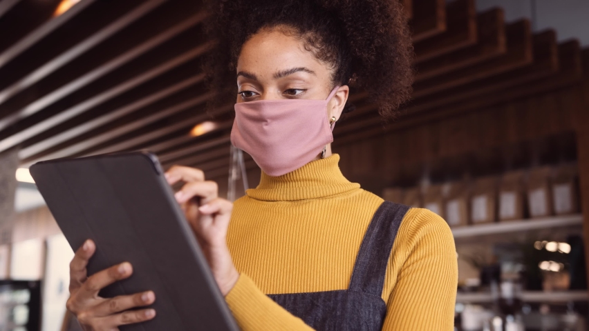 Female African coffee shop owner wearing face mask standing in front of counter using digital tablet for stock check. At owners Coffee shot Royalty-Free Stock Footage #1058419378