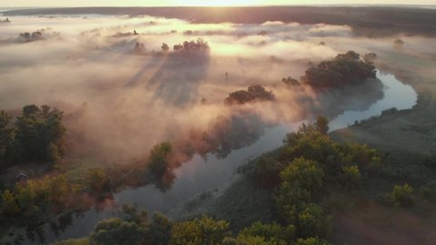 Aerial drone view of sunrise over misty river. Calmness, relaxation, meditation, solitude, beauty of nature concept