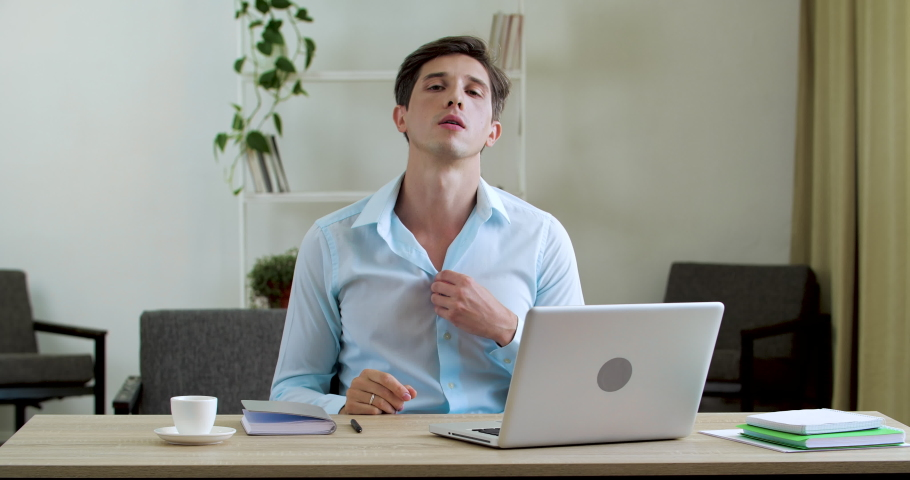 Male worker tired sitting in office without air conditioning ventilation problems, feeling irritated, exhausted from heat, suffering from high air temperature, picking up notebook waving creating wind Royalty-Free Stock Footage #1058432647