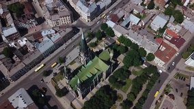 Old catholic church, street traffic life and buildings. Drone aerial video of Saint Olga and Elizaveta Church in central part of old city of Lviv, Ukraine.