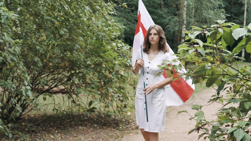 Beautiful young Female in white dress walking and holding belarusian flag during Protests in Belarus. Opposition against government and president