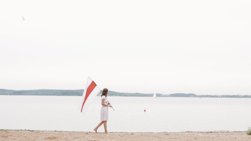 Beautiful slim female in white dress walking near the sea with belarusian White red white flag. Protests in Belarus against dictatorship. Freedom in Belarus