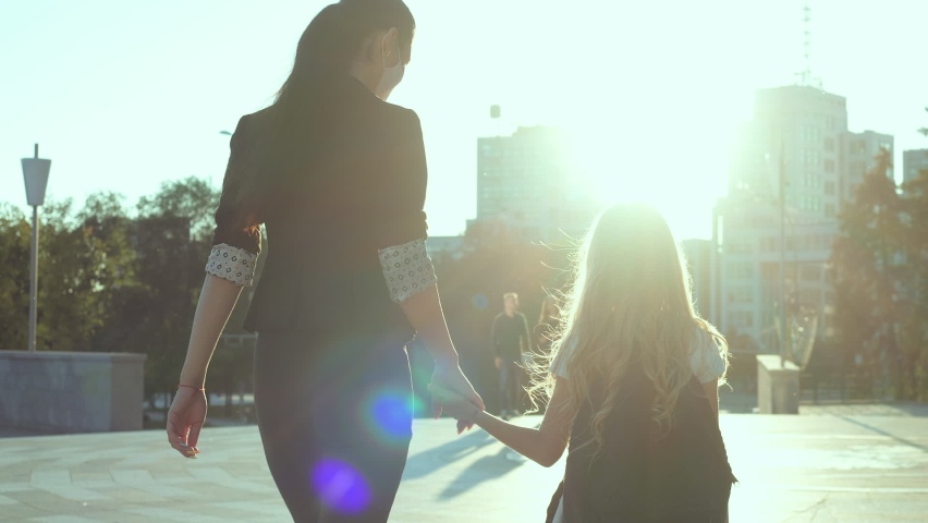Back view young woman in black business suit and mask holds little girl in white dress by hand, go in city to school study, elementary class. Pupil wears large backpack goes home with mum together Royalty-Free Stock Footage #1058439862