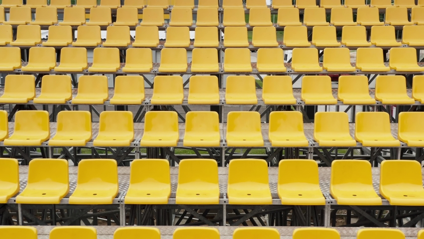 Aerial view drone flies over empty stadium or race track seats during coronavirus COVID-19 pandemic. Rows and yellow seats without viewers and spectators | Shutterstock HD Video #1058441494