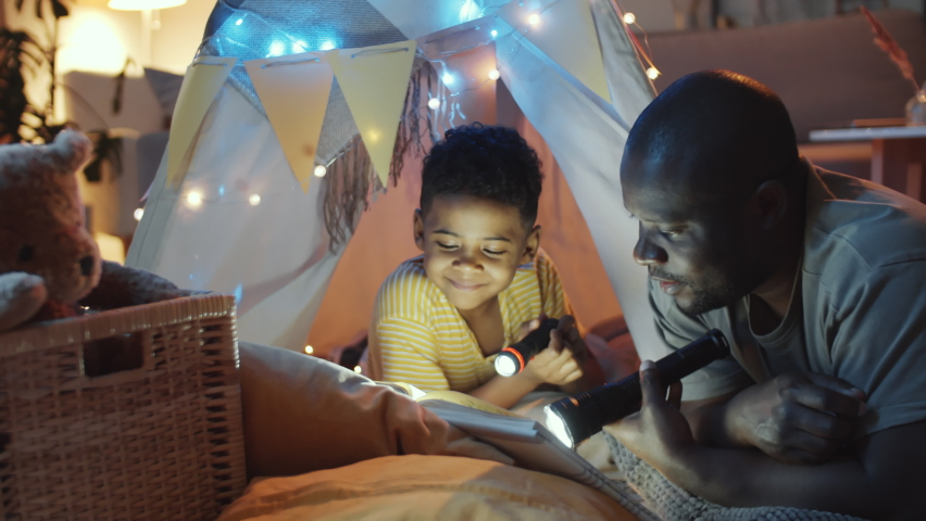 Joyous African American dad and little son holding flashlights, reading book, chatting and laughing while he lying in teepee tent decorated with lights in dark room in the evening