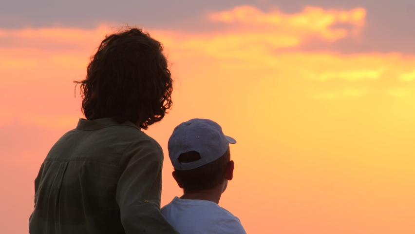 Happy mother holding her son on the knees at sunset near the sea. Interpersonal communication. Woman holds kid on her knees and watching amazing sunrise over the sea, city. Happy childhood background