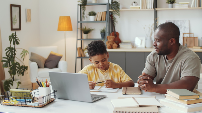 African American father sitting with little son at table in the living room, pointing on laptop screen and explaining homework to kid as he taking notes Royalty-Free Stock Footage #1058443630