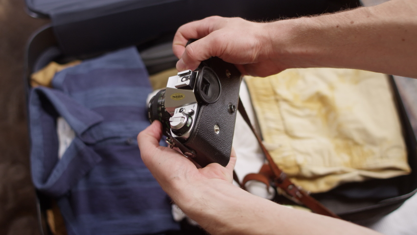 Man checks his old film camera before packing it in a suitcase