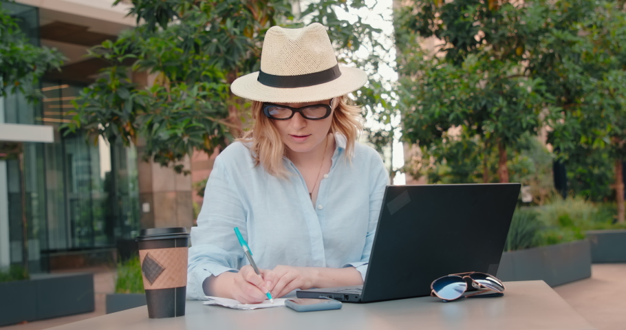 Serious female entrepreneur writing down to do list to achieve her goals. Woman working in the outdoor business park on laptop. Business woman is planning agenda of professional business meeting, 4K.  | Shutterstock HD Video #1058452372