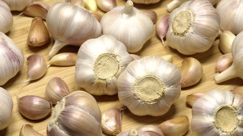 Fresh garlic bulbs and cloves on wooden table rotation background. Loop motion