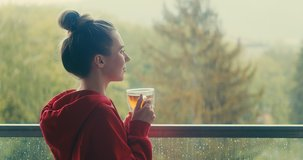 Woman drinks tea a cup, and relax on terrace at home in autumn rainy day. Health care, authenticity, sense of balance and calmness. Work from home. 4K Video