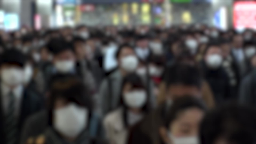 TOKYO, JAPAN - MARCH 2020 : Crowd of people walking at the station in morning rush hour. Commuters going to work. People wearing mask to protect from Coronavirus (COVID-19). Blurred slow motion shot.   Shutterstock HD Video #1058456362