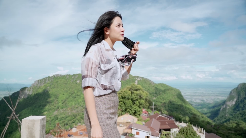 Asian young woman remove face mask and feel the fresh air standing on top of the mountain stretch, corona covid-19 pandemic, air pollution problem, feeling fresh air without mask, new normal life