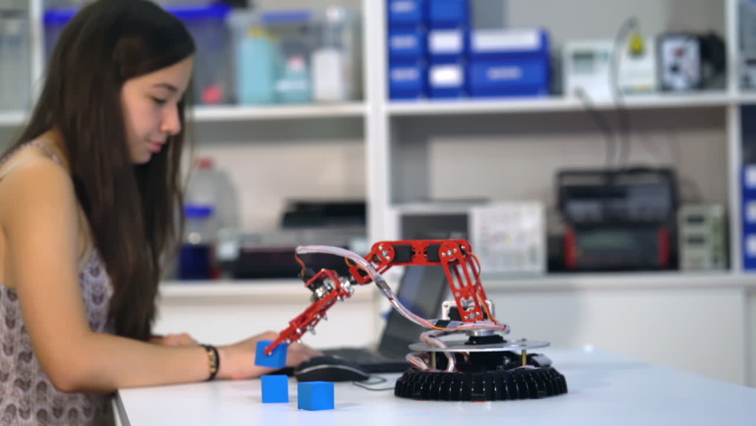 Experiment with intelligent manipulator. industrial robot model. Robot with optical recognition system, School girl in robotics laboratory   Shutterstock HD Video #1058469037