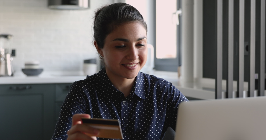 Smiling indian woman shopping online using laptop paying with credit card, buy remotely. Happy 30s female purchasing on website, use internet banking secure system, makes quick instant payment concept Royalty-Free Stock Footage #1058470678