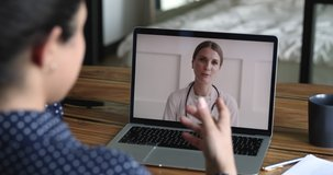 Therapist cardiologist provide medical heart disease consultation to client by video call, laptop screen view over patient shoulder sit at desk got help from woman practitioner doctor in white coat