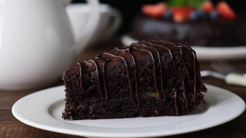 Eating chocolate cake. Taking ]bite of moist delicious chocolate cake with a fork