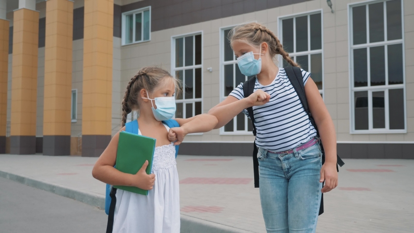 Girls say goodbye near the school with their elbows. Social distance at school. New normalcy. Safe communication of dreaming children in medical masks. Children's greetings from afar. School dream kid Royalty-Free Stock Footage #1058474668