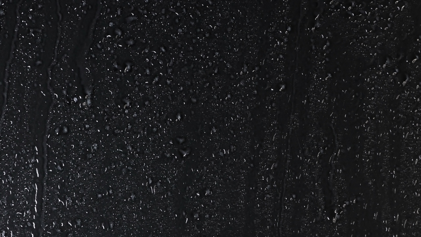 4K High quality footage of Rain on Window Sky Drops, White Drops of rain trickling down on black background. Rain Drops Falling down on black background.  Close up Slow Rain in slow motion.  Droplets