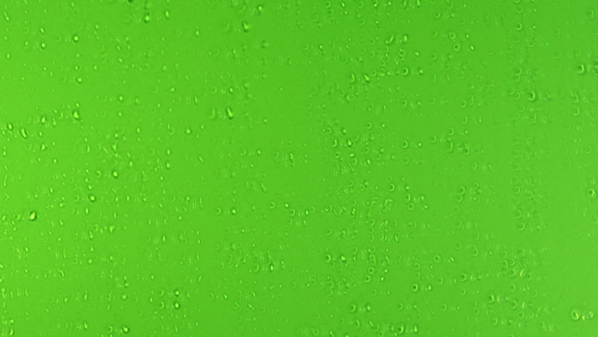 Drops trickling down on green background. Rain Drops Stock Footage in 4K. Droplets of water on green glass background. Rain Drops Falling down on green background. Close up drops on glass or bottle.