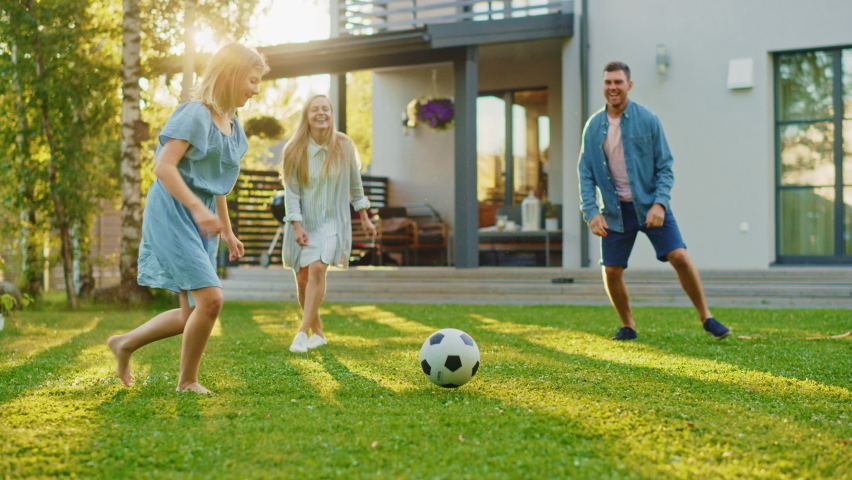 Happy Family of Four Playing Soccer, Passing Football to Each Other. Mother, Father, Daughter and Son Have Fun Playing Games in the Backyard Lawn of Idyllic Suburban House on Sunny Summer Day | Shutterstock HD Video #1058475676