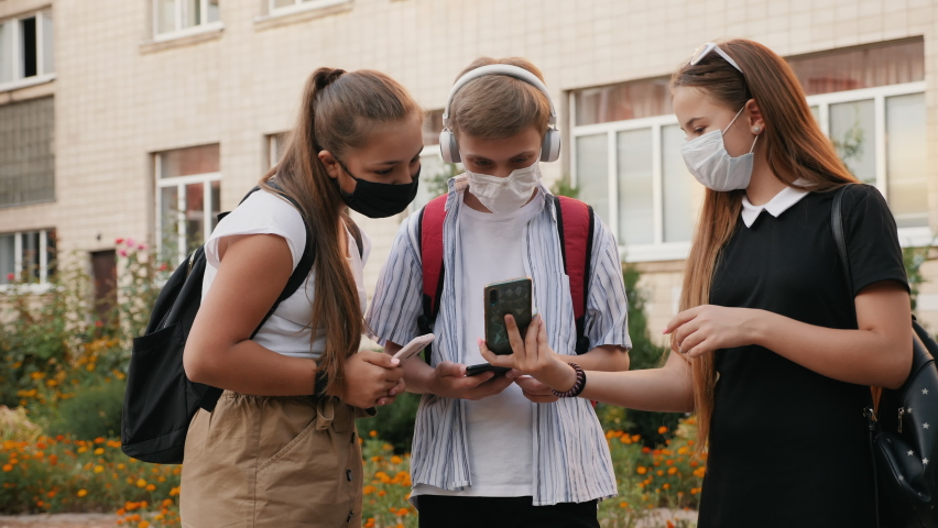 Schoolchildren wearing protective medical masks communicate in the school yard, use smartphones. Education during the coronavirus pandemic Royalty-Free Stock Footage #1058478310