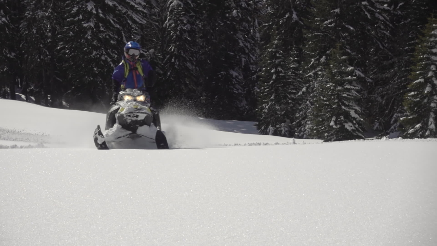 500 FPS SLO MO: Man snowmobiles up hill and makes powder turn with Grand mountains in background. snowmobilers sports riding. bright skidoo motorbike and suit. Pro snowmobiler, Winter fun moto extreme | Shutterstock HD Video #1058483671