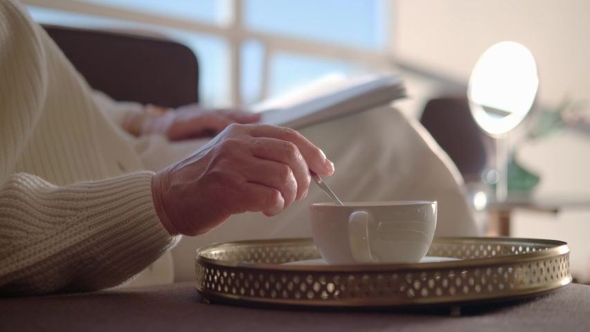 Relaxation time: A mature woman sits in an armchair reading a magazine and stirring sugar in a coffee mug. Only hands in the frame, no face. An adult woman drinks coffee in a sunny room. | Shutterstock HD Video #1058484046