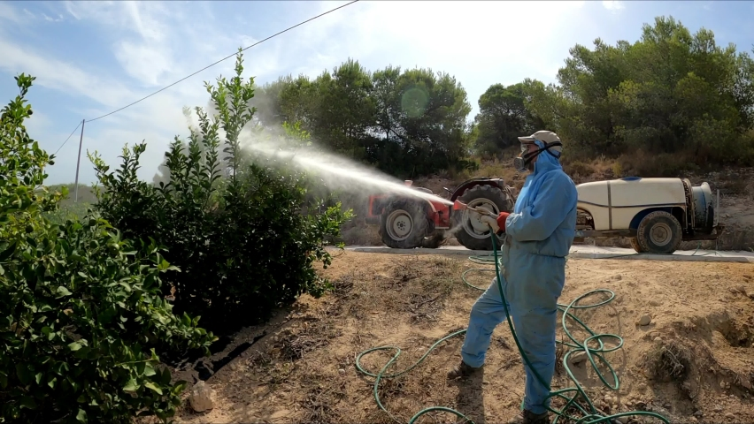 Farmworker spray ecological pesticide in lemon trees. Farmer fumigate in protective suit and mask lemon trees. Man spraying toxic pesticides, pesticide, insecticides  Royalty-Free Stock Footage #1058489770