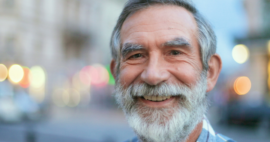 Close up of face of senior Cauasian man with gray hair and beard. Portrait of handsome old grandfather looking at side ad then turning face to camera with smile at street in town. Outdoors. | Shutterstock HD Video #1058490907