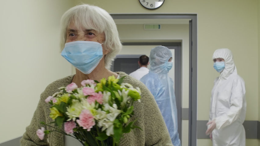 Senior woman in medical face mask waving to doctor and nurses in protective uniforms, then walking with flowers through corridor while leaving hospital after covid-19 recovery