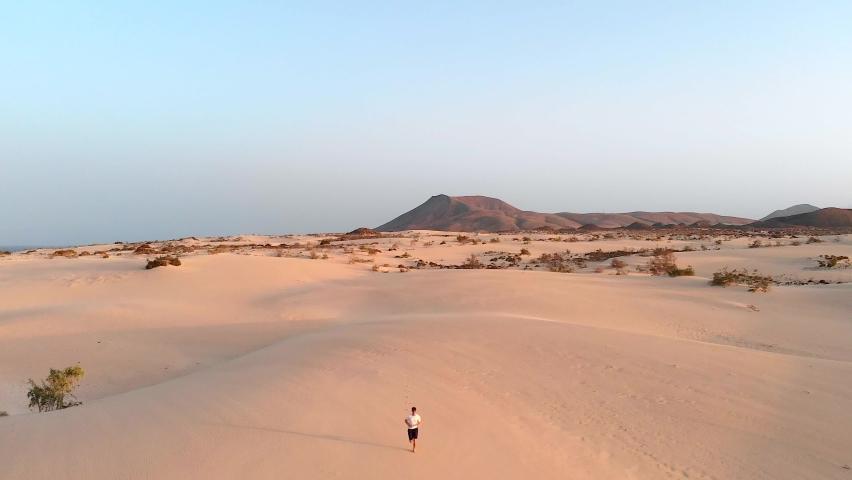 Man Running Alone In The Desert at Golden Hour. | Shutterstock HD Video #1058492065