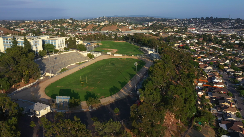 Drone Flies Towards High School with Football field During Sunset over Surburban Los Angeles Village, California, USA
