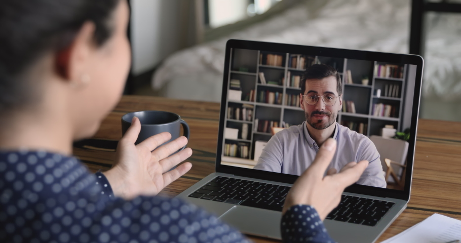 Job interview by videocall, hiring concept. Due corona virus or covid-19 businesspeople negotiate remotely use video conference app, laptop screen view over girl shoulder sit at desk talk by videocall Royalty-Free Stock Footage #1058504074