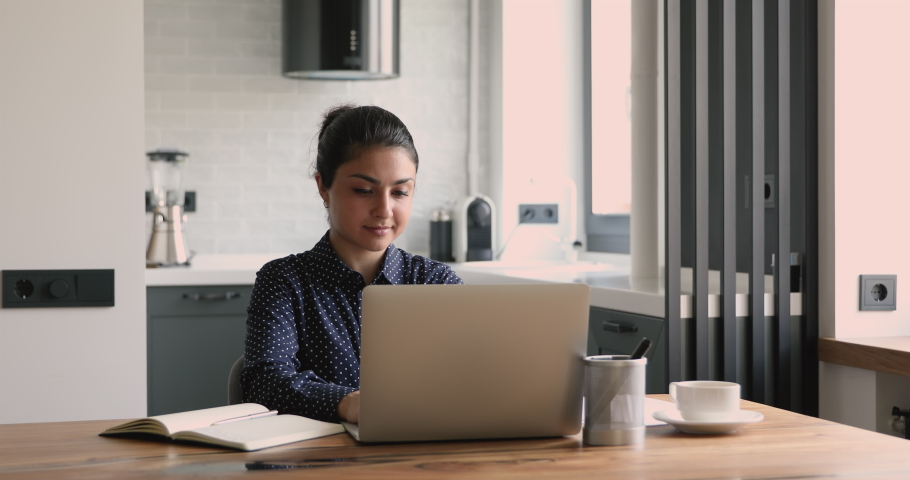 Thoughtful indian businesswoman sit at desk work on laptop faced the challenge in thoughts stares out window. Pensive female looking away think of problem search for solution, inspiration new ideas Royalty-Free Stock Footage #1058504089