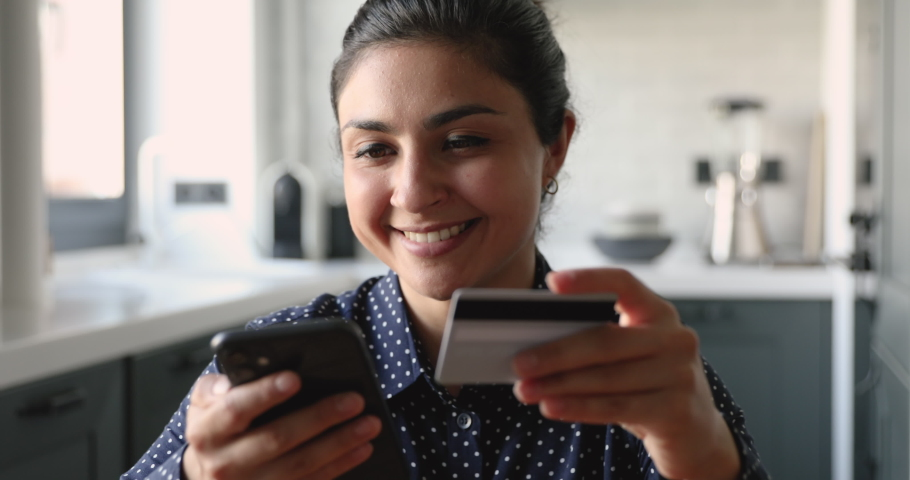 Close up attractive indian female buyer sit at home use cell phone hold card enjoy internet shopping easy convenient method of instant distance payment and purchase using modern wireless tech concept Royalty-Free Stock Footage #1058504119