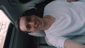 Smiling man driver making a selfie or video call while sitting in a car. Young male traveler doing a video chat from his car. Vertical video.