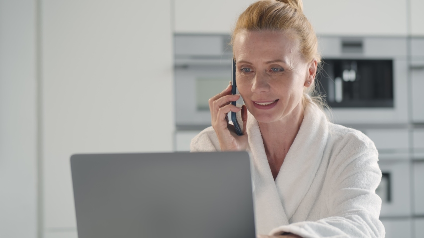 Senior woman in bathrobe talking on mobile phone using laptop at home. Portrait of middle-aged businesswoman talking on smartphone with client reading information on computer screen sitting in kitchen