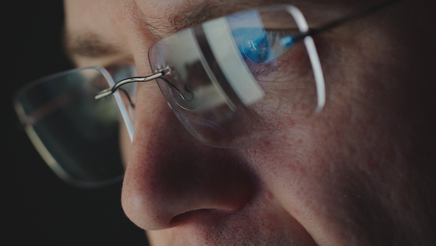 REFLECTION: Close Up of face of adult man in an eyeglasses looking a website | Shutterstock HD Video #1058520121