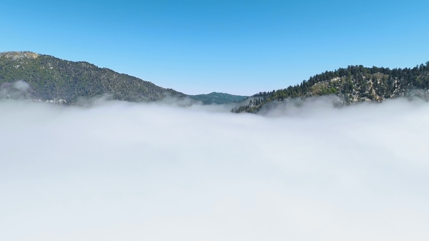 The drone hovers over the wooded hills and flies right into the the clouds in Californa, USA | Shutterstock HD Video #1058523268