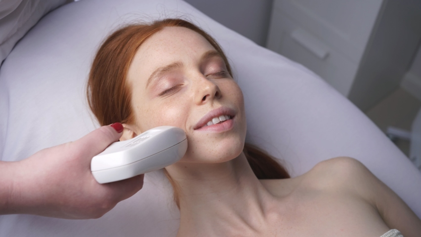 Young woman in the office of a cosmetologist receives fractional mesotherapy of the face. Facial skin rejuvenation. | Shutterstock HD Video #1058525584