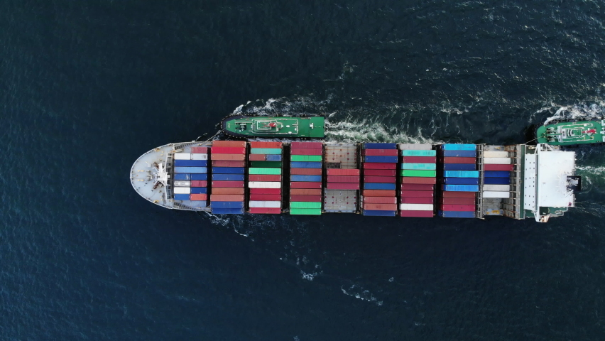 Aerial top view of cargo ship carrying container and running with tug boat for export  goods  from  cargo yard port to custom ocean concept freight shipping by ship . Royalty-Free Stock Footage #1058526400