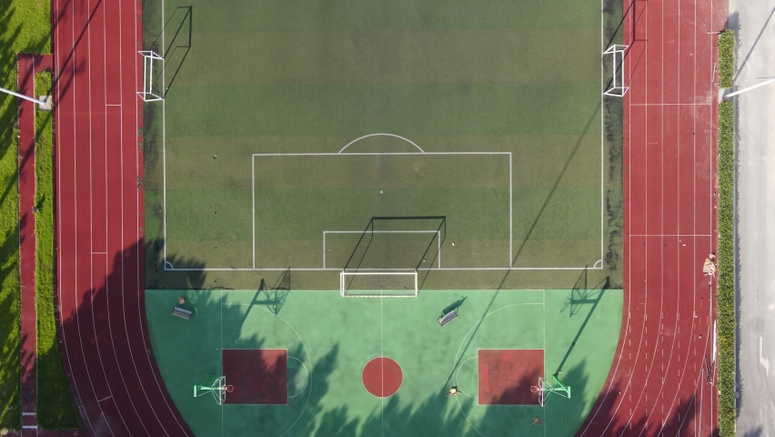 Aerial view drone flying close to empty soccer goal, football field during sunset in the stadium. No people view in summer, sports soccer recreation concept footage. Red racing track Shanghai China.   Shutterstock HD Video #1058527219