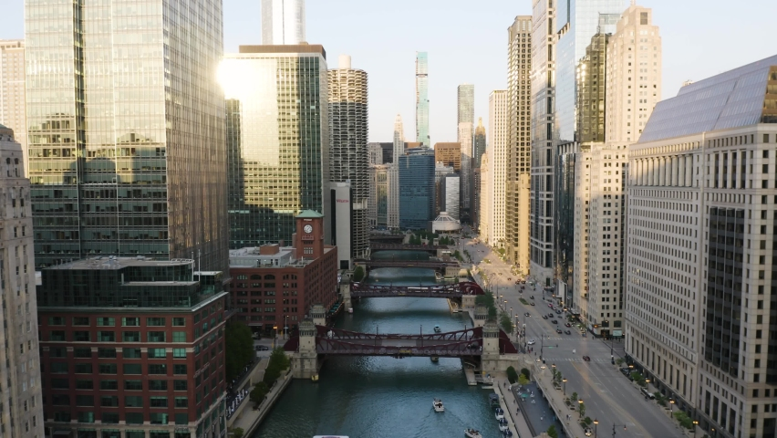 Drone Flies Backwards as Train Crosses Bridge over River in Downtown Chicago Loop