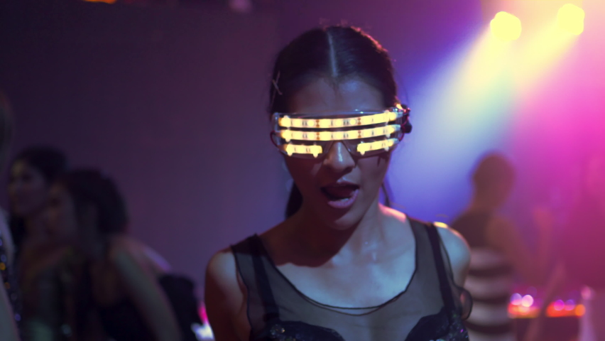 Confidence woman with LED glowing glasses dancing to the music played by dj with multi-color illuminated at night club. Group of  beautiful woman enjoy nightlife and having fun with disco dance party.