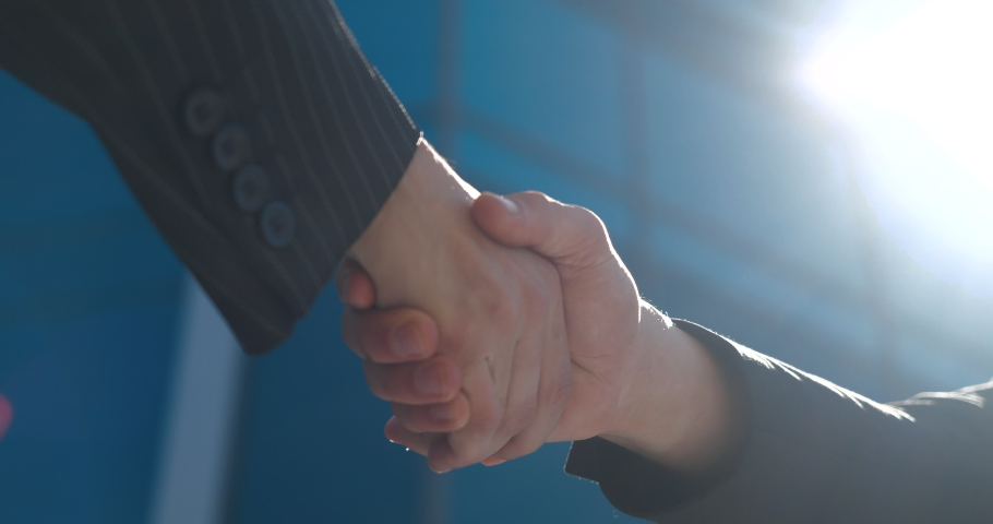 Closeup part of human body two men shake hands, conclude successful contract agreement, sign of support for partnership cooperation, businessmen in black jackets greet on street with male arms gesture