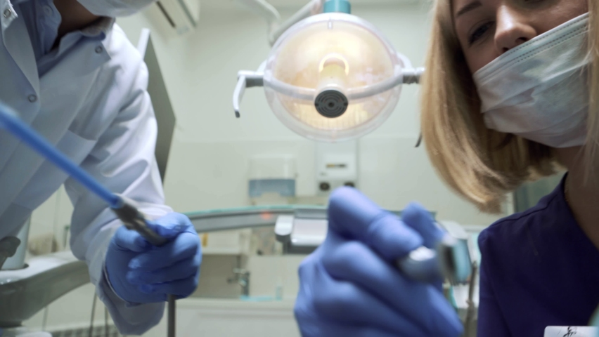 First person view. Female dentist and her assistant start working. In the dental office, lamp turning on, the adjutant helping the patient. Doctor working with instruments. Concept of healthy teeth. | Shutterstock HD Video #1058533066